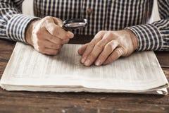 Periódico de la lectura del hombre con magnificar Fotografía de archivo