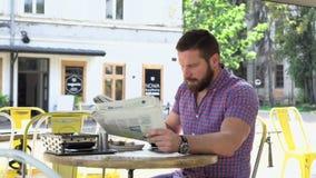 Periódico de la lectura del hombre durante el desayuno metrajes