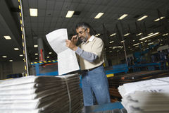 Periódico de la lectura del hombre en fábrica Imágenes de archivo libres de regalías