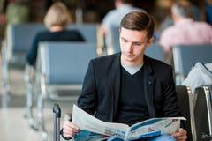 Periódico de la lectura del hombre joven en el aeropuerto mientras que espera el embarque Chaqueta del traje del hombre de negoci Fotografía de archivo