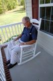 Periódico de la lectura del hombre mayor en el pórche de entrada Imagen de archivo libre de regalías