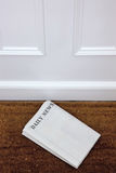 Periódico en blanco que miente en un doormat. imagenes de archivo