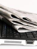Periódico en la computadora portátil Imágenes de archivo libres de regalías