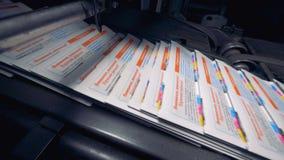 Periódico en una oficina de la impresión, cierre para arriba Las porciones de periódico cubren ir en un transportador en una inst almacen de video