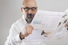 Periódico envejecido medio de la lectura del hombre fotografía de archivo