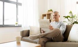 Periódico feliz de la lectura del hombre en casa Fotografía de archivo libre de regalías