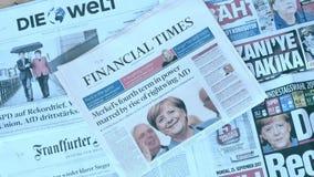 Periódico internacional de la prensa que divulga sobre la elección de Angela Merkel en el enfoque-hacia fuera de Alemania almacen de video