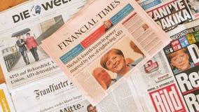 Periódico internacional de la prensa que divulga sobre la elección de Angela Merkel en el enfoque-hacia fuera de Alemania almacen de metraje de vídeo