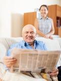 Periódico maduro feliz de la lectura de los pares junto Fotos de archivo libres de regalías