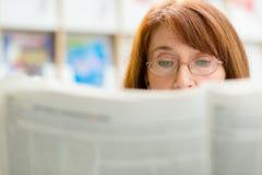 Periódico mayor de la lectura de la mujer en biblioteca foto de archivo libre de regalías