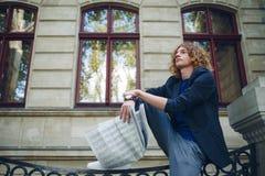 Periódico rojizo joven de la lectura del hombre cerca del edificio del viejo estilo foto de archivo libre de regalías
