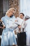 periódico serio de la lectura de la mujer y el hablar por el teléfono del vintage mientras que comida de la tenencia del marido d imagen de archivo libre de regalías