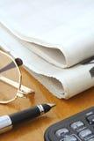 Periódico, vidrios, pluma y calculadora Foto de archivo