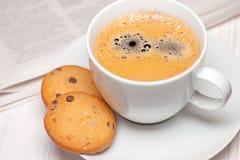 Periódico y café con las galletas Foto de archivo