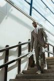 Periódico y cartera de la tenencia del traje del hombre de negocios que llevan afroamericano mientras que camina imagen de archivo libre de regalías