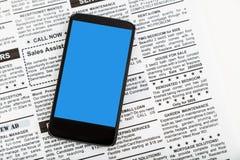 Periódico y smartphone falsos Imagen de archivo libre de regalías