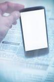 Periódico y smartphone falsos Imágenes de archivo libres de regalías