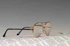 Periódico y vidrios Imagen de archivo libre de regalías