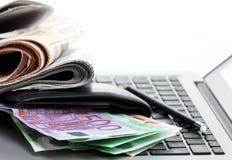 Periódicos de la pizca de las ganancias del comercio electrónico, y dinero en un ordenador portátil Imágenes de archivo libres de regalías