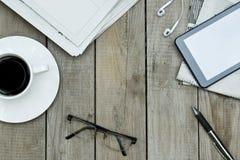 Periódicos, tableta digital y taza de café en la tabla de madera imagen de archivo libre de regalías