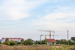 Peri urban scenery of the suburb of Belgrade, with cranes on a construction site in the middle of fields royalty free stock photography