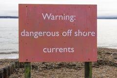 Pericoloso d'avvertimento fuori dal segno delle correnti della riva Fotografie Stock