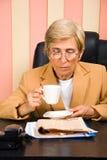 Periódico mayor de la lectura de la mujer de negocios en oficina Imagen de archivo