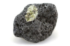 Peridot crystal and lava rock. A small piece of lava rock with a greenish crystal inclusion - known as peridot. Handpicked from a beach on Lanzarote in the stock photography