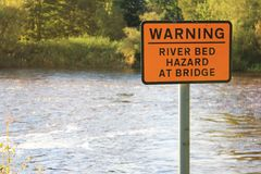 Perigo de advertência da cama de rio no sinal da ponte Fotografia de Stock Royalty Free