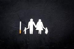 Perigo do fumo Cigarro perto da silhueta da família no espaço preto da opinião superior do fundo para o texto Fotos de Stock