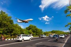 Perigo plano que aterra perto da estrada na ilha tropical Bali, aeroporto de Ngurah Rai, Tuban, regência de Badung, Bali, Indonés foto de stock