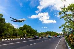 Perigo plano que aterra perto da estrada na ilha tropical Bali, aeroporto de Ngurah Rai, Tuban, regência de Badung, Bali, Indonés Fotografia de Stock