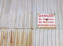 Perigo, sinal não fumadores na cerca do ferro ondulado imagens de stock