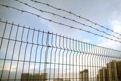 Perimeter fence. With the city buildings on the background Royalty Free Stock Photos