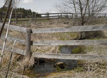 The Perimeter. Rural fence surrounding grassy acreage with small stream Stock Photo