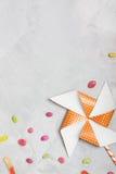 Perinola anaranjada con las estrellas y los caramelos del blanco en backgr concreto Imágenes de archivo libres de regalías