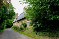 Quaint period cottage with a thatched roof seen in summer, in rural Britain. Stock Images