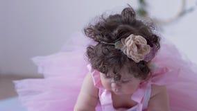 Perioden för fotoet för barn` s, lilla flickan med stora ögon och lockigt hår i rosa färger klär närbilden som poserar i den vita lager videofilmer