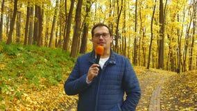 Periodista adulto con el micrófono que trabaja en parque almacen de metraje de vídeo