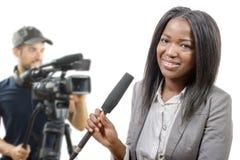 Periodista afroamericano joven con un micrófono y una cámara Fotografía de archivo