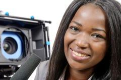 Periodista afroamericano joven con un micrófono y una cámara Imagenes de archivo