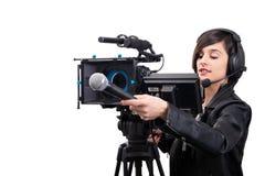 Periodista bonito de la mujer joven con el micrófono con la cámara de vídeo en blanco foto de archivo libre de regalías