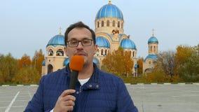 Periodista con el micrófono delante de la iglesia metrajes