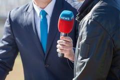 Periodista con entrevistarse con del micrófono Imagenes de archivo