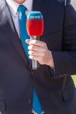 Periodista con la información del micrófono Imágenes de archivo libres de regalías