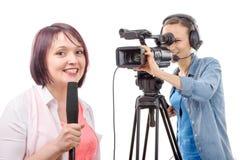 Periodista de la mujer joven con un micrófono y un camerawoman Imagen de archivo libre de regalías