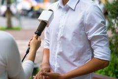 Periodista de las noticias con el micrófono que se entrevista con en el primer de la calle Foto de archivo