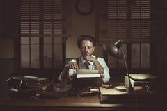 periodista de los años 50 en su oficina tarde en la noche Foto de archivo