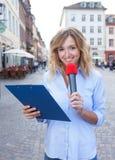 Periodista de sexo femenino con el micrófono en la ciudad Imagenes de archivo