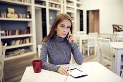 Periodista de sexo femenino que tiene charla del teléfono con el redactor explaying Fotografía de archivo